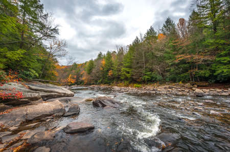 Autumn colors abound along a wild river with rapids in the Appalachian mountains Stok Fotoğraf