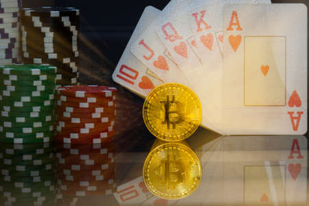 golden Bitcoin in front of a royal flush in hearts and gambling zoomed into the arrangement Stock Photo