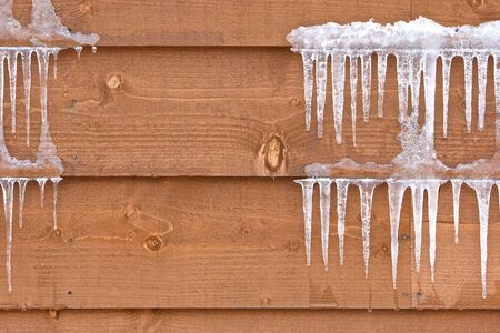 Icicles hang from a wood cabin in on a chilly winter day in Hokkaido, Japan photo