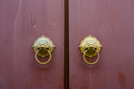 Old Chinese red gate doors with lion door knob photo