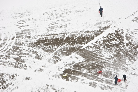 Communal services worker in uniform shoveling snow in winter snowstorm photo