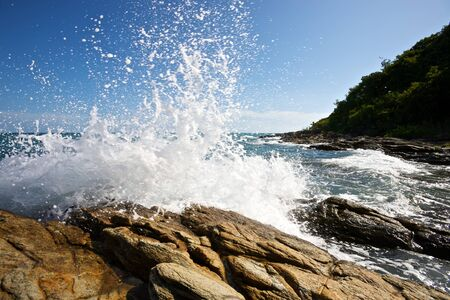 The waves breaking on a stony beach, forming a spray