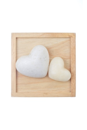 two white heart shaped stones on wood background photo
