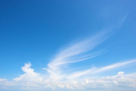 wing-shaped cloud in bright blue sky photo