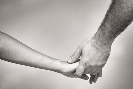 couple holding hands: monotone shot of couple holding hands Stock Photo