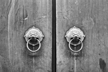 monochrome shot of chinese door with a lion or dragon head