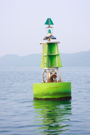 green navigational buoy for boating traffic on the sea Stock Photo
