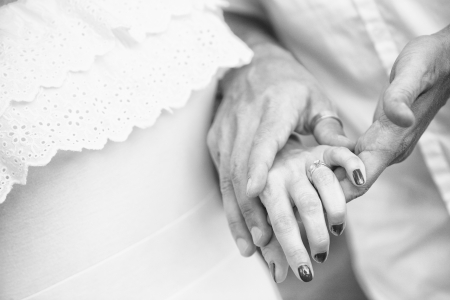 monotone shot of couple holding hand with the diamond ring photo