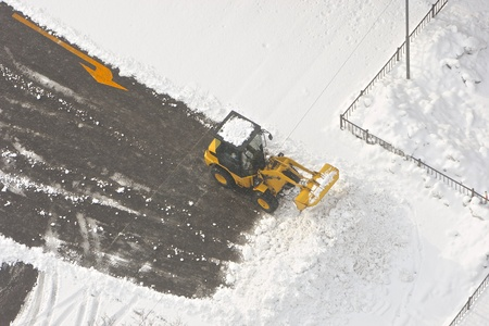 wheel loader machine removing snow on the road at winter day photo
