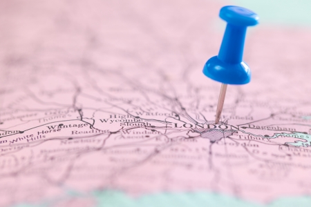 close up shot of push blue pin pointing on the map at London for travel background photo