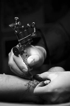 monochrome shot of a tattoo artist tattooing cover up on an ankle with shallow depth of field and some vignette