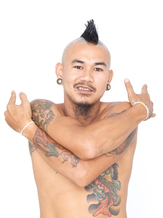 portrait of smiling asian punk guy hugging himself with mohawk hair style, ear piercing and tattoo isolated on a white background Stock Photo - 21848037