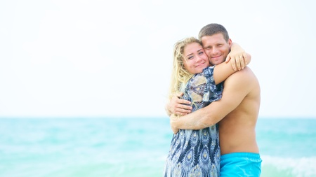 portrait of a happy couple in love hugging on the beach at summer time