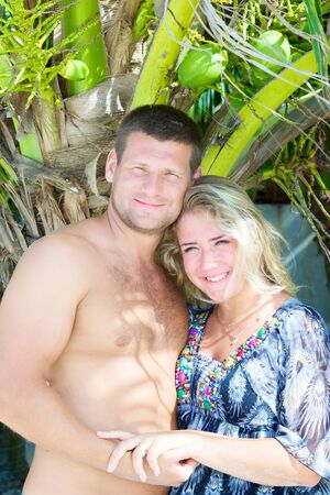 portrait of a happy couple in love with tropical palm tree on the beach at summer time