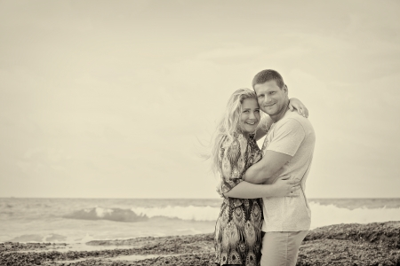 monotone shot of a happy couple in love on the beach, vintage style, with some vignette photo