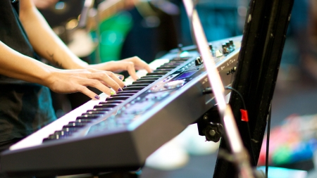 hands of musician playing keyboard in concert with shallow depth of field, focus on right hand