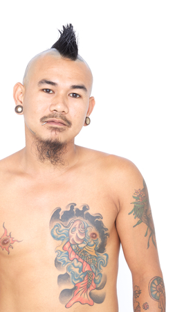 portrait of asian punk guy with mohawk hair style, piercing and tattoo isolated on a white background photo