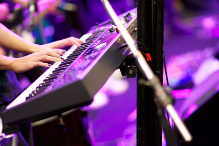 hands of musician playing keyboard in concert with shallow depth of field, focus on right hand photo