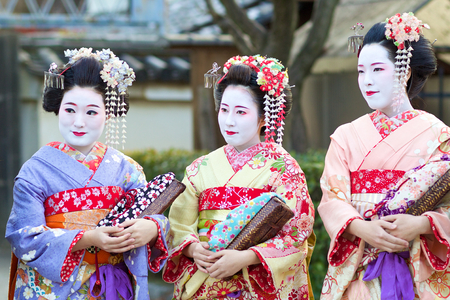 Kyoto, Japan - February 20, 2014: three young beautiful Japanese women called Maiko wear a traditional dress called Kimono on February 20, 2014 at Gion, Kyoto, Japan.