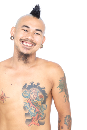 portrait of smiling asian punk guy with mohawk hair style, piercing and tattoo isolated on a white background photo