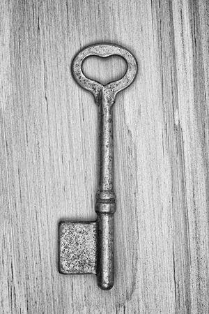 key hole shape: monochrome shot of an old key with heart shape ring hole on wood texture background