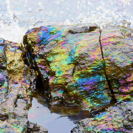 rainbow reflexió nyers olajfolt a kövön a strandon