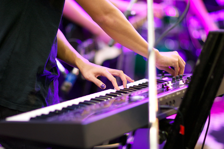 keyboard player: hands of musician playing keyboard in concert with shallow depth of field, focus on left hand Stock Photo