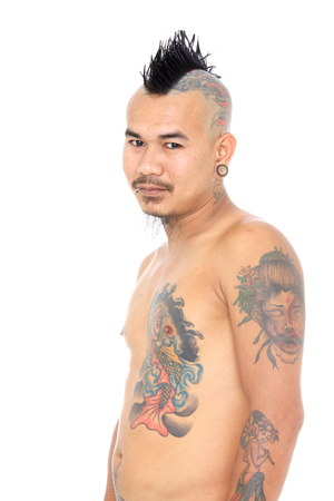 portrait of smiling asian punk guy with mohawk hair style, piercing and tattoo isolated on a white background Stock Photo