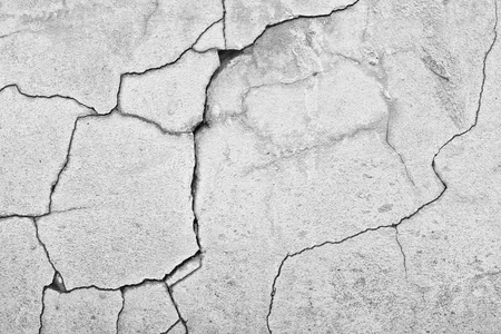 black and white shot of cracked concrete wall texture background Stock Photo