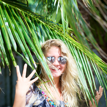 portrait of young beautiful woman in sunglasses with tropical palm tree on the beach at summer day, square ratio Stock Photo