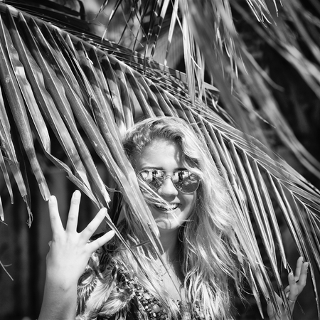 portrait of young beautiful woman in sunglasses with tropical coconut palm tree on the beach at summer day, monochrome, black and white, vintage style
