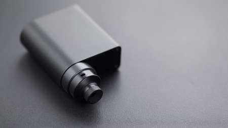 high end rebuildable dripping atomizer with black regulated box mods on black texture background, vaping device, selective focus with shallow depth of field Imagens