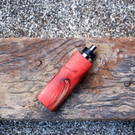 high end red natural stabilized wood box mods with rebuildable dripping atomizer on old wood texture background, vaping device, selective focus
