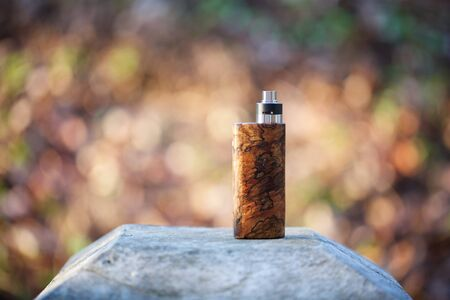 high end natural stabilized wood box mods with rebuildable dripping atomizer on bokeh texture background, vaping device, selective focus