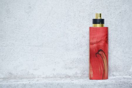 high end red natural stabilized wood box mods with rebuildable dripping atomizer on white concrete wall texture background, vaporizer equipment, selective focus Banque d'images