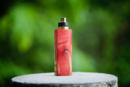 high end red and natural stabilized wood box mods with gold and black rebuildable dripping atomizer, vaporizer equipment, selective focus