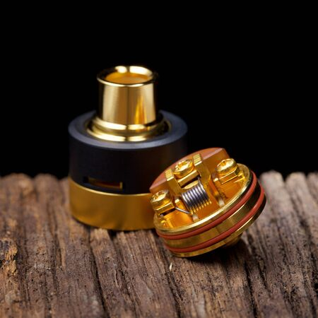 close up, macro shot of high end rebuildable dripping atomizer for flavour chaser on natural wood texture background, vaping device, selective focus