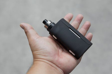 high end black regulated box mods with rebuildable dripping atomizer in hand on light grey texture background, vaping device, selective focus