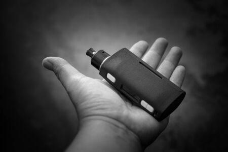 black and white, monochrome shot of high end regulated box mods with rebuildable dripping atomizer in hand, vaping device, selective focus
