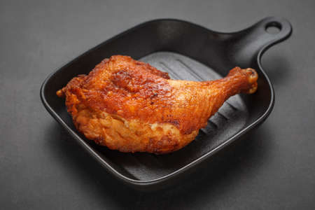 fried chicken with black pan on the dark tone texture background