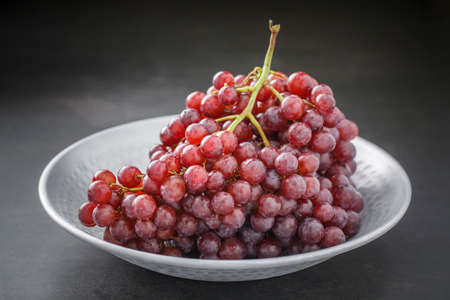fresh red grape in nice metal plate on dark grey tone texture background