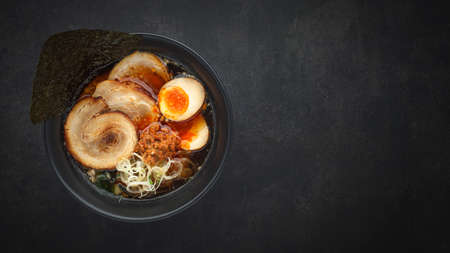 top view Asian ramen noodle soup with Chashu (Japanese braised pork belly), Nitamago egg, sliced spring onion, Ajitsuke Menma and dried seaweed on dark texture background with copy space for text 免版税图像