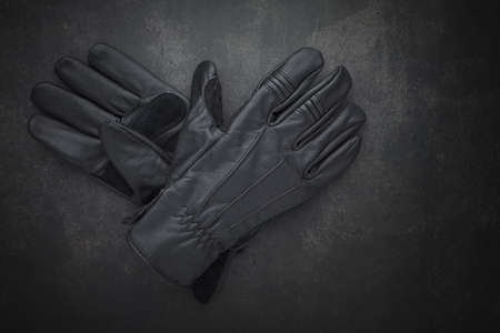 top view shot a pair of new black leather motorcycle gloves classic style for protect biker hands on dark gray, grey, black tone texture background with copy space for text