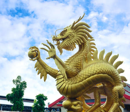 Golden dragon sculpture holding a crystal ball and a beautiful sky.