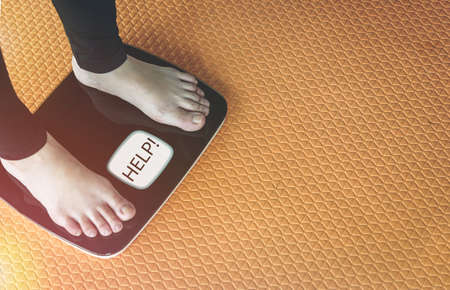 An Asian woman's feet are on a scales.