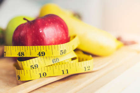 Yellow measuring tape surrounded by red apples.Health Care and Weight Management Concepts Stock Photo