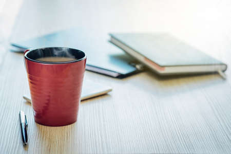 The reddish brown coffee cup is on the wood table and pen, the diary book is blurred background. 免版税图像