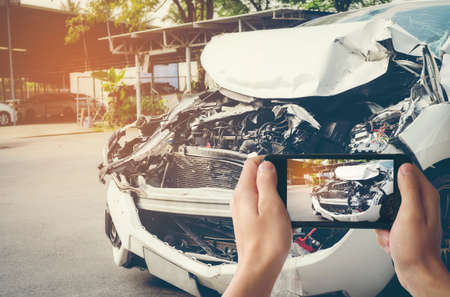 A man photographed his vehicle with accidental damage with a smart phone.Car Insurance Concept Reklamní fotografie