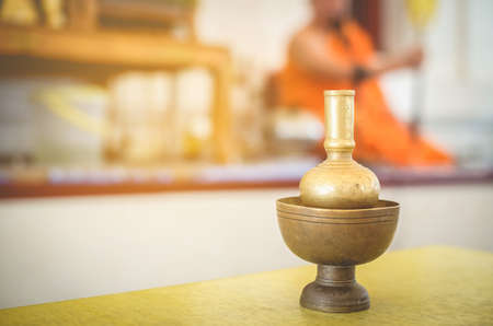 The equipment used in the rituals of Buddhism by the priests yellow dress, orange is the background blurred.