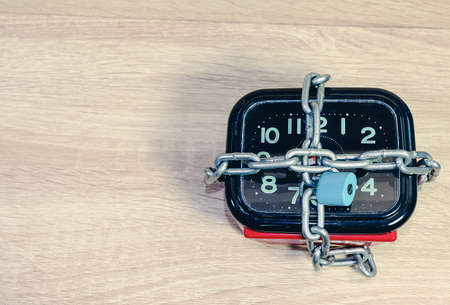 Stopping the time.Old red and black clock with a chain and lock,on wooden floor background. Banco de Imagens